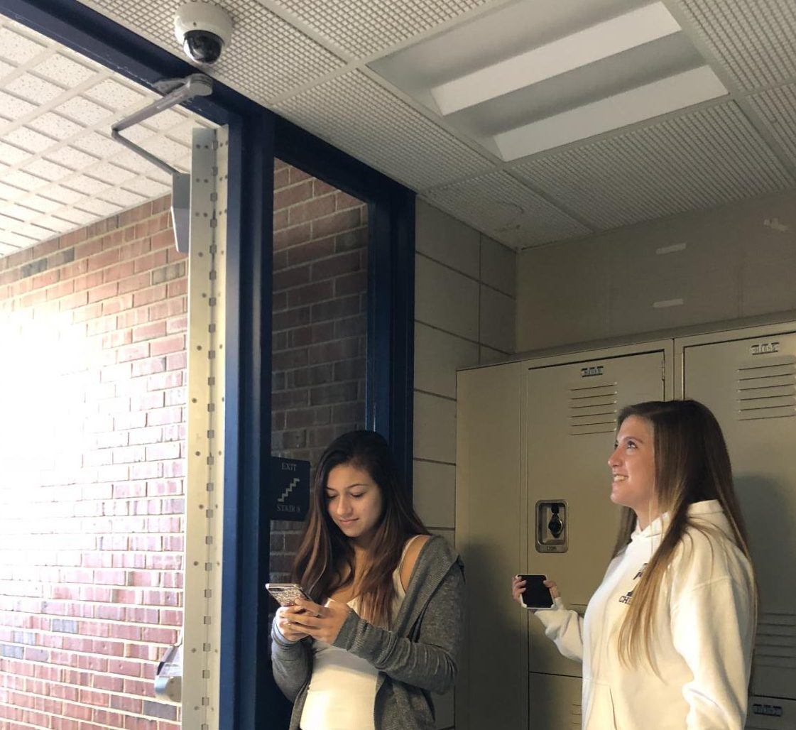 Students Lindsey Gardella, left, and Erin Drew stand beneath one of Tritons new cameras.
