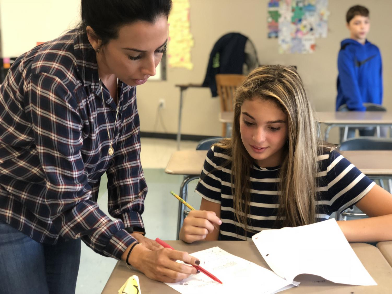 Seventh grade teacher Ms. Christina Thomas looks over a test with a student.