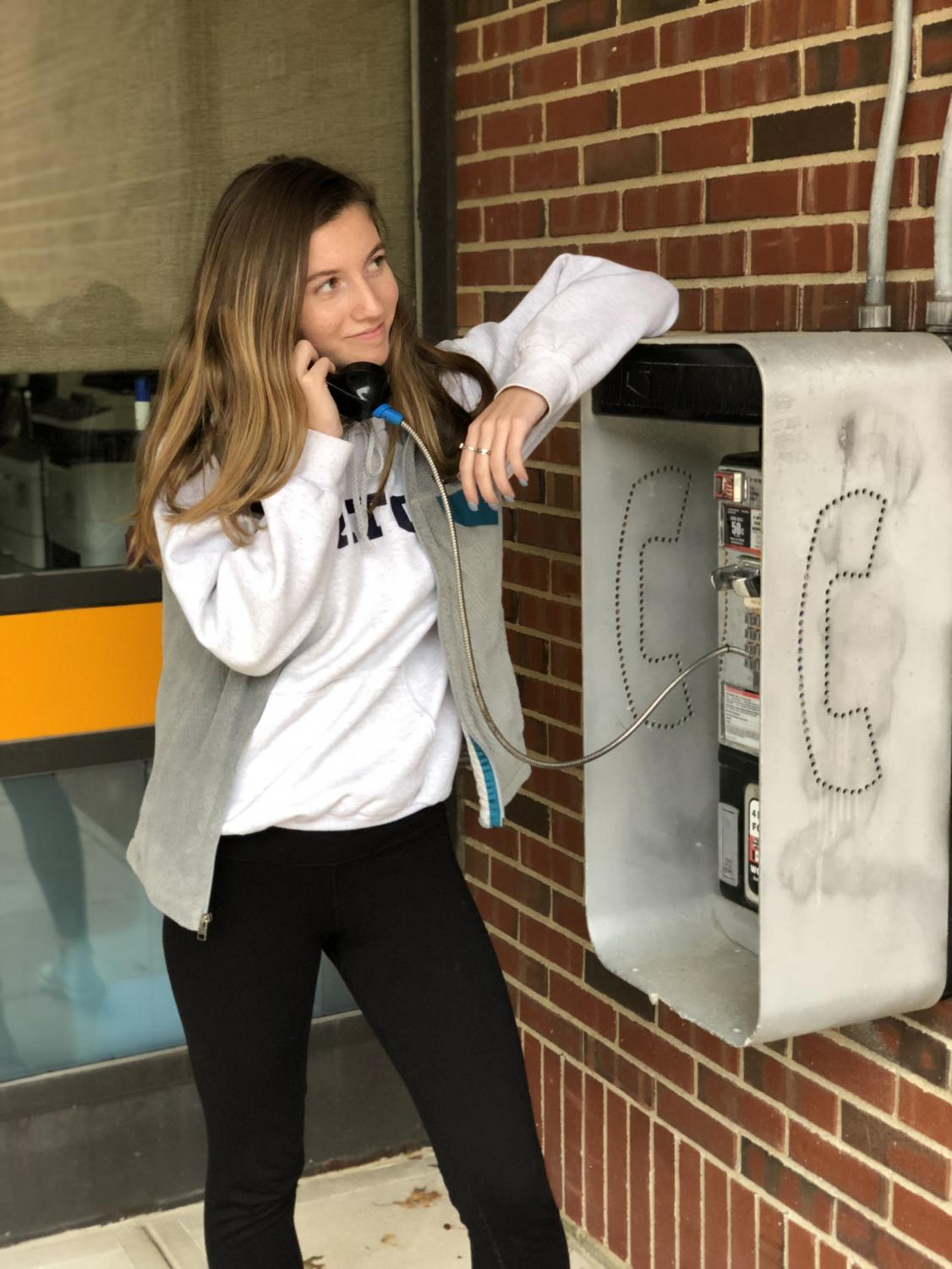 Senior Mackenna Faucher making a call on the Triton Payphone.
