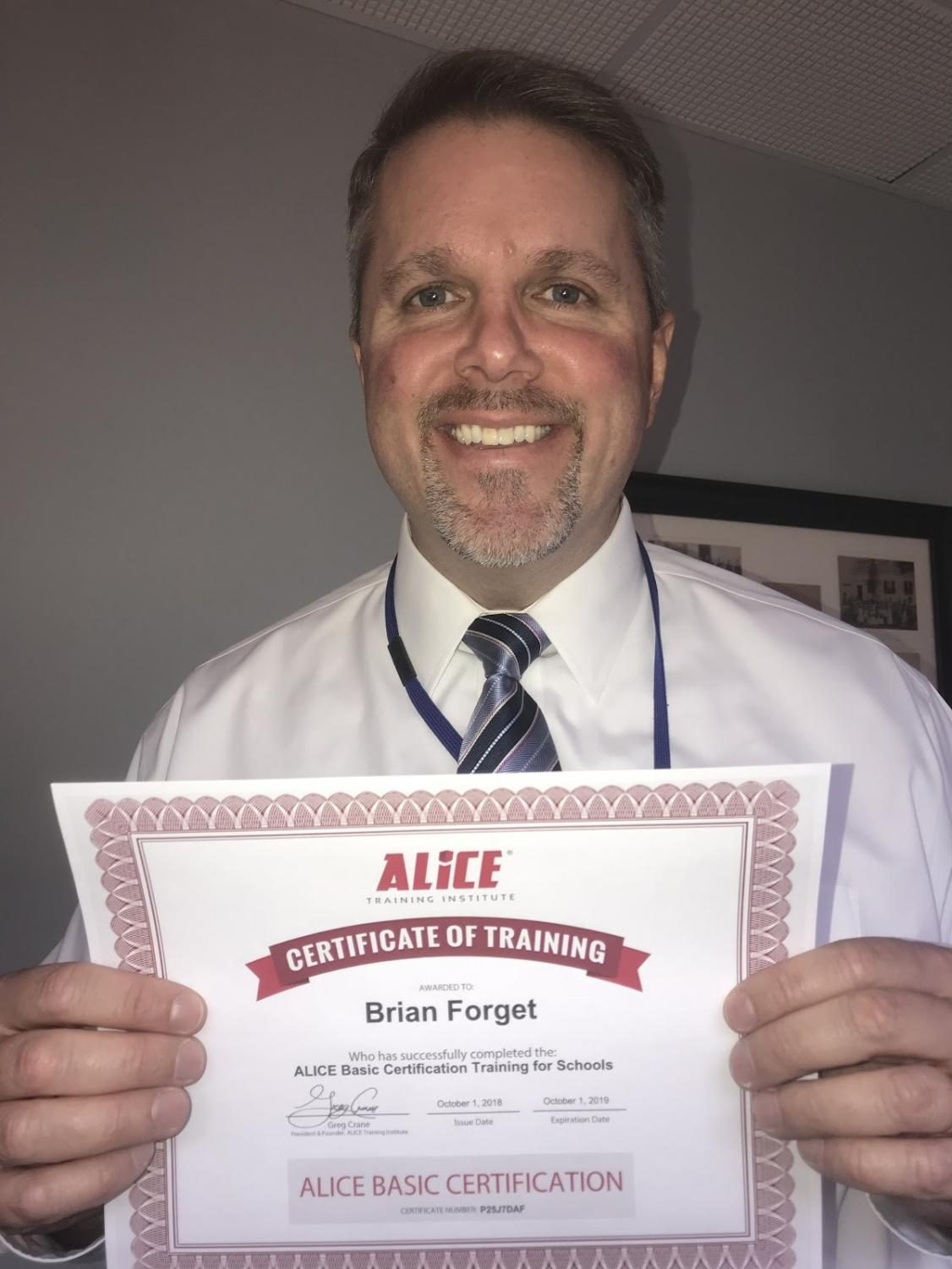 Brian Forget, the Superintant of Triton Regional School District holding his ALICE training certificate.
