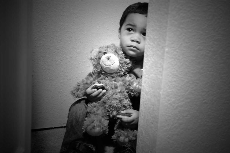 A child is shown scared in the act of child abuse.