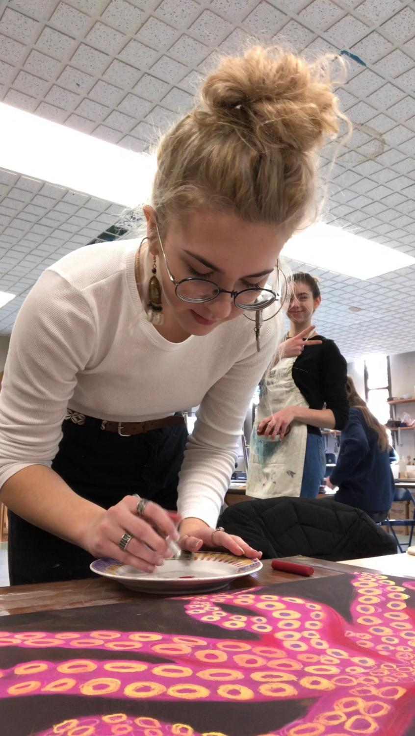 Senior Lydia Crowley puts finishing touches on an art project.