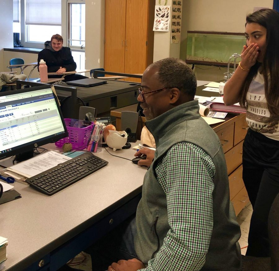 Mr. Ivan Ferron enters his grades into Aspen as student Komal Patel looks on at the end of the day. Report cards for second quarter are due on next week.