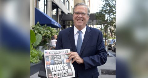 Jeb Bush pictured holding up a New York Times Article regarding Donald Trump, not knowing it was he who was in the hot seat