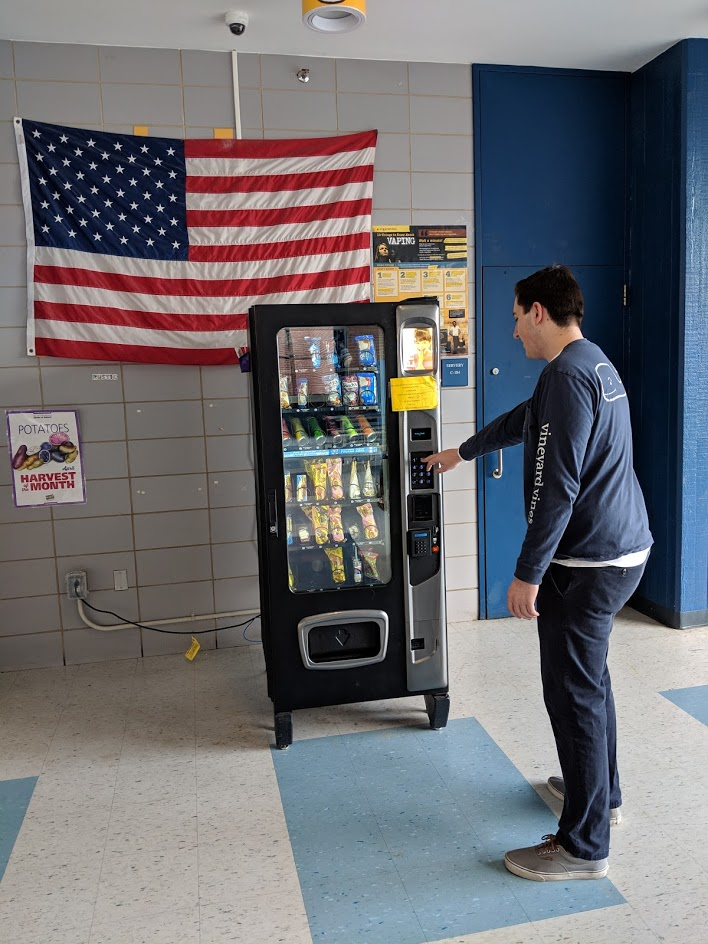 Senior Josh Lind using the the vending machine in the cafeteria to purchase a snack for third period.