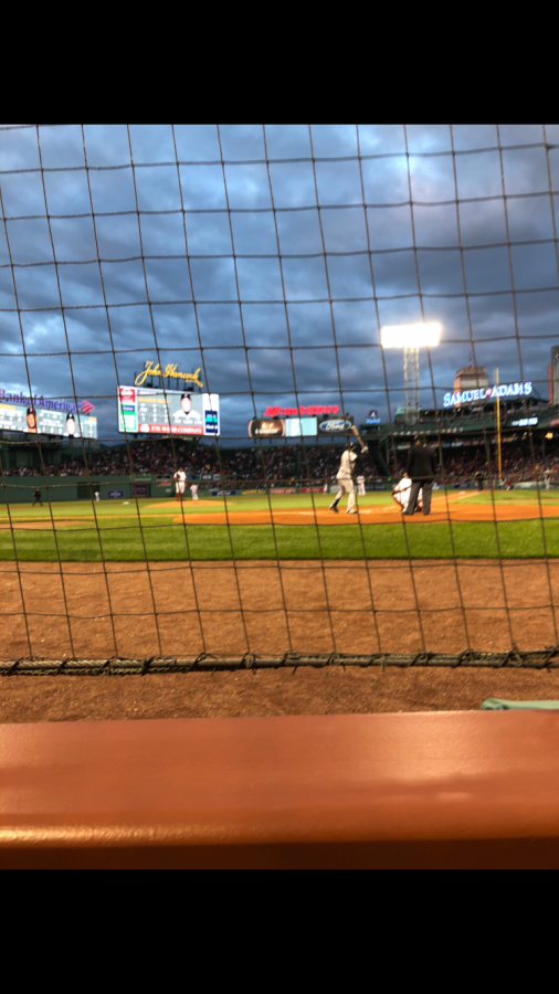 From+behind+home+plate%2C+a+fan+watches+the+Red+Sox+just+as+the+lights+come+on+at+Fenway+Park.