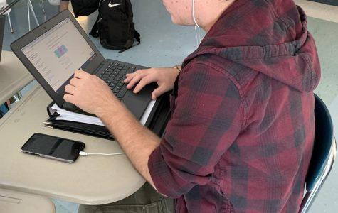 Junior Anthony Mariniello listens to music while doing work in Algebra 2.