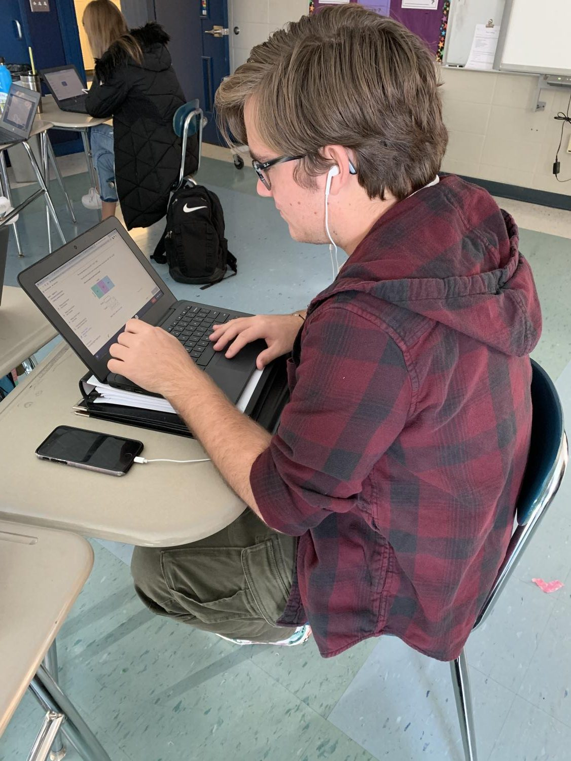 Junior Anthony Mariniello listens to music while doing work in Algebra 2.