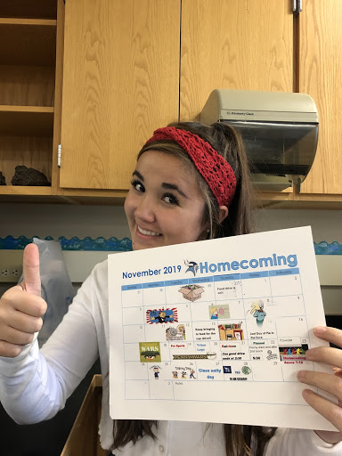 Riley McLaughlin holding the printed schedule for the 2019 homecoming week.