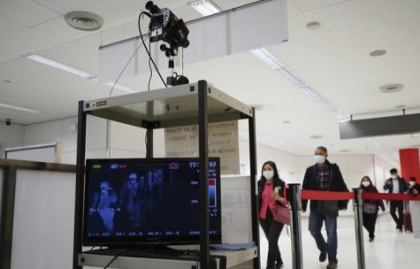 Travelers from Wuhan and other cities in China go through body temperature scanners at an airport near Tokyo.