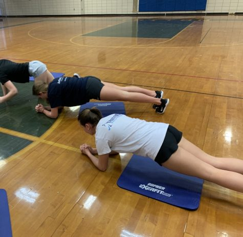 Freshman Chloe Connors and Ally Pugh doing a core workout to get ready for their upcoming lacrosse season