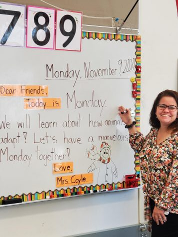 Mrs. Tara Coyle stands before one of her classroom boards in her new class this fall