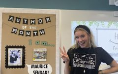 Ms. Gross in her library standing in front of her newly decorated sign.